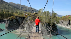 Young boy walking  through a rope bridge over the river in mountains Stock Footage