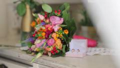 Bridal Bouquet bouquet and Wedding rings on the table Stock Footage