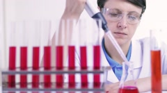 Female research assistant, goggles pour red liquid automatic pipette tube rack - stock footage