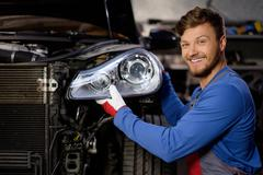 Mechanic with new car headlight in a workshop - stock photo
