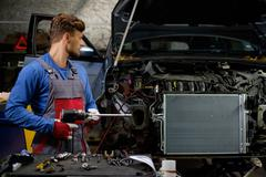 Mechanic with pneumatic tool in a workshop Stock Photos