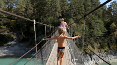 Child and his mother walking  through a rope bridge over the river in mountains. Stock Footage