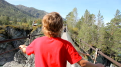 Boys walking  through a rope bridge over the river in mountains Stock Footage