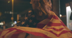 Woman draped with American flag on city street at night Stock Footage