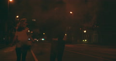 Teenagers running down city street with smoke flares at night Stock Footage