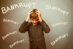 Teen boy businessman fails bankrupt holding his head inscription Stock Photos