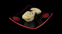 Tamago sushi omelette on black plate rotating Stock Footage