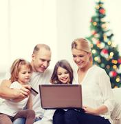 Happy family with laptop computer Stock Photos