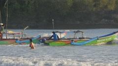 Men sail to sea while lady tourist swims,Pangandaran,Java,Indonesia Stock Footage