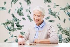 Stock Photo of senior woman putting money to piggy bank at home