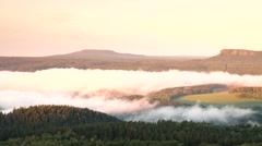 Sunrise in a beautiful rocky park at Czech Germany border. Hilly peaks in fog Stock Footage