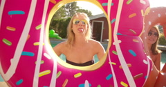 Smiling girl friends with funny pool inflatables outdoors Stock Footage
