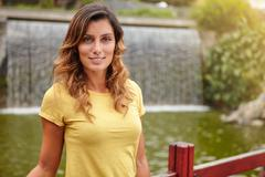 Stock Photo of Waist up portrait of a young woman looking at camera near park waterfall