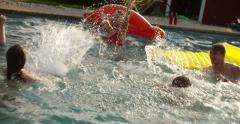 Teen friends splashing in a pool with colourful inflatables Stock Footage