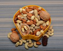 Set of Dry Fruits in a Bowl & around on Table - stock photo