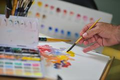 Artist's hand applying paint gouache on the drawing sheet - stock photo