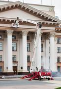 Builders paint building facade by fire truck Kuvituskuvat