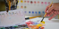 Artist's hand applying paint gouache on the drawing sheet Stock Photos