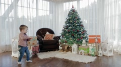 cheerful boy near Christmas tree rejoice - stock footage