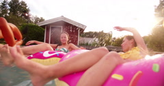 Girls playfully splashing in a backyard pool together in summer - stock footage