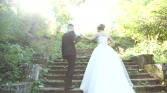 The bride and groom up the old stairs Stock Footage