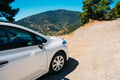 White color small hatchback car on Spainish nature mountains lan - stock photo
