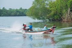 Thai man rides long tail boat in Tha Thong, Thailand. Stock Photos