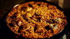 Paella with rabbit, chicken and shrimp close up. - stock footage