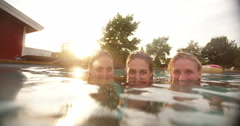 Portrait of three girls submerged in swimming pool at sunset - stock footage