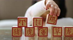 Young girl stacking Chinese blocks - stock footage