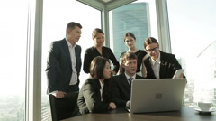 A young promising team of businessmen working on laptop and looking at the Stock Footage