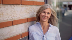 Mature woman with grey hair on a city street smiling Stock Footage