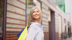 Mature woman walking with shopping bags and waving goodbye - stock footage