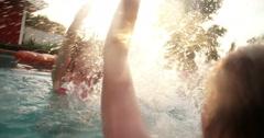 Summer swimming pool with girls splashing water playfully Stock Footage