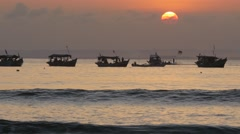 Sunset with fisher boats and surf at sea,Pangandaran,Java,Indonesia Stock Footage