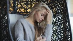 pretty blonde sitting in a wicker chair and touches her hair - stock footage