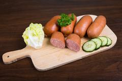 Sausages arranged on cutting board with lettuce - stock photo