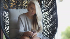 Pretty blonde sitting in a wicker chair and typing a message on your phone Stock Footage