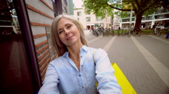 Mature woman with grey hair taking a selfie on a city street Stock Footage