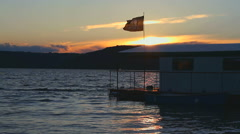 Houseboat with Jolly Roger on a sunset Stock Footage