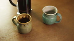 Stock Video Footage of Coffe pours into two mugs, close up.