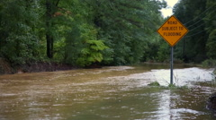Flooded road zoom in to sign Stock Footage