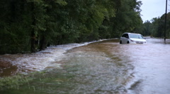 Flooded road w van stuck push in Stock Footage