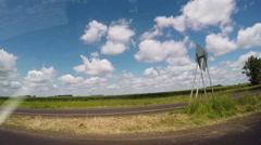Drive near corn field with wind turbines in distance. Stock Footage