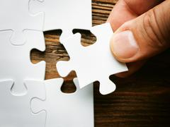 Hand with missing jigsaw puzzle piece. Business concept image for completing Stock Photos