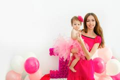 mother holding a baby in her arms. Little girl in a pink skirt. On a light - stock photo