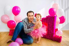 father holding a baby in her arms. Little girl in a pink skirt. On a light - stock photo