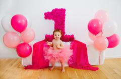 First birthday.Baby in fluffy pink skirt, with balloons and a big Digits 1 - stock photo