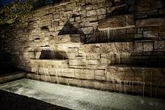 Glowing night shot of water cascading down brick wall to rectangular pool - stock photo
