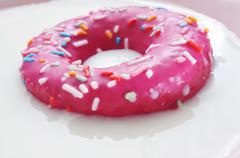 Pink donut being soaked in milk Stock Photos